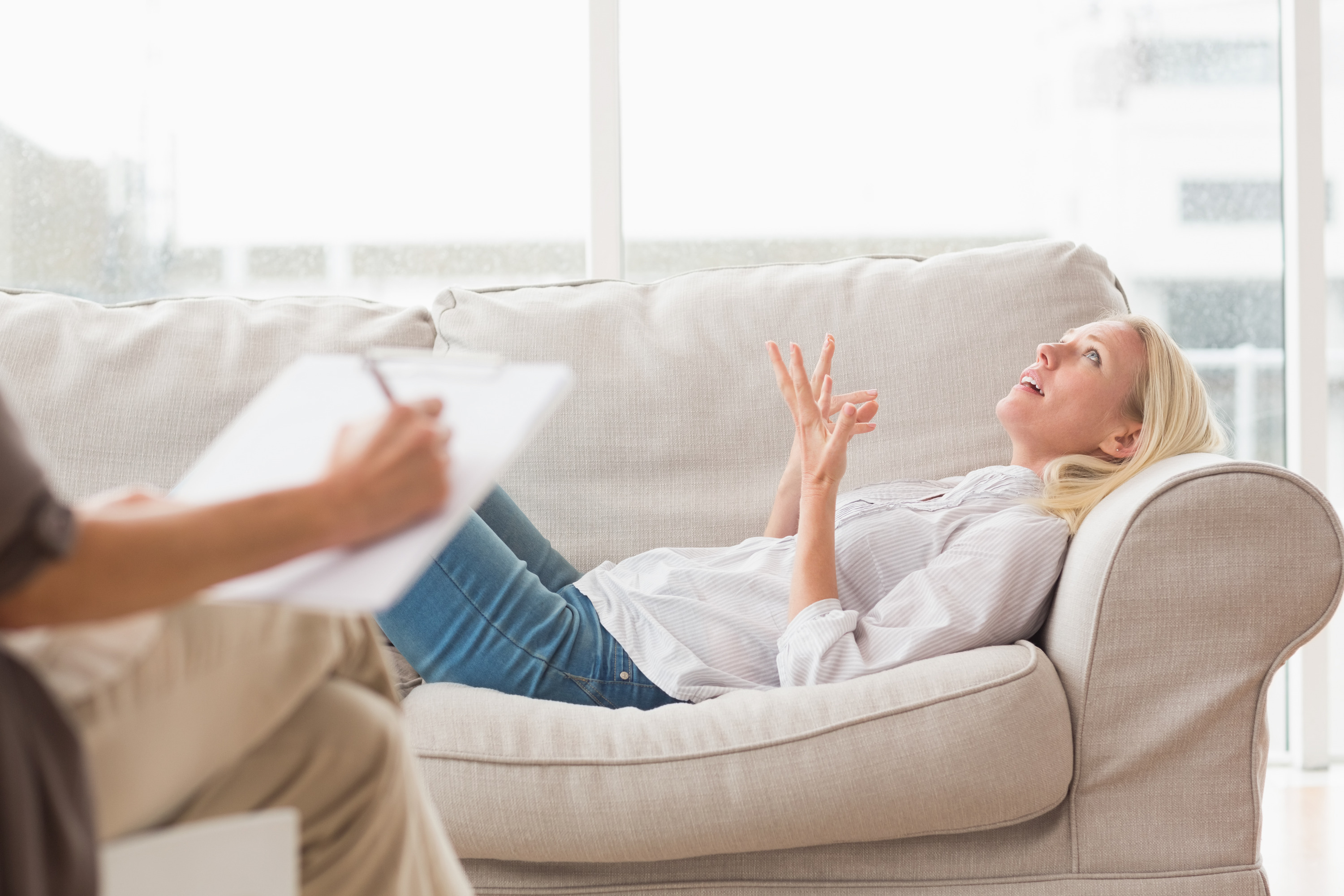 Depressed woman speaking to therapist while she is taking notes